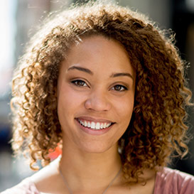 Young woman with brown curly hair smiling