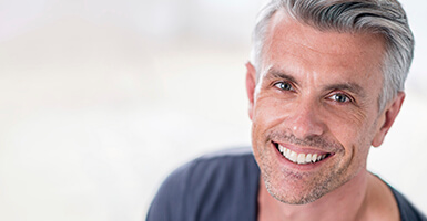 Grey haired man with a grey shirt smiling