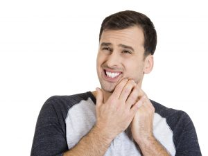 man in pain pressing jaw