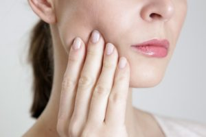 WOman with slight pain due to chipped or broken tooth