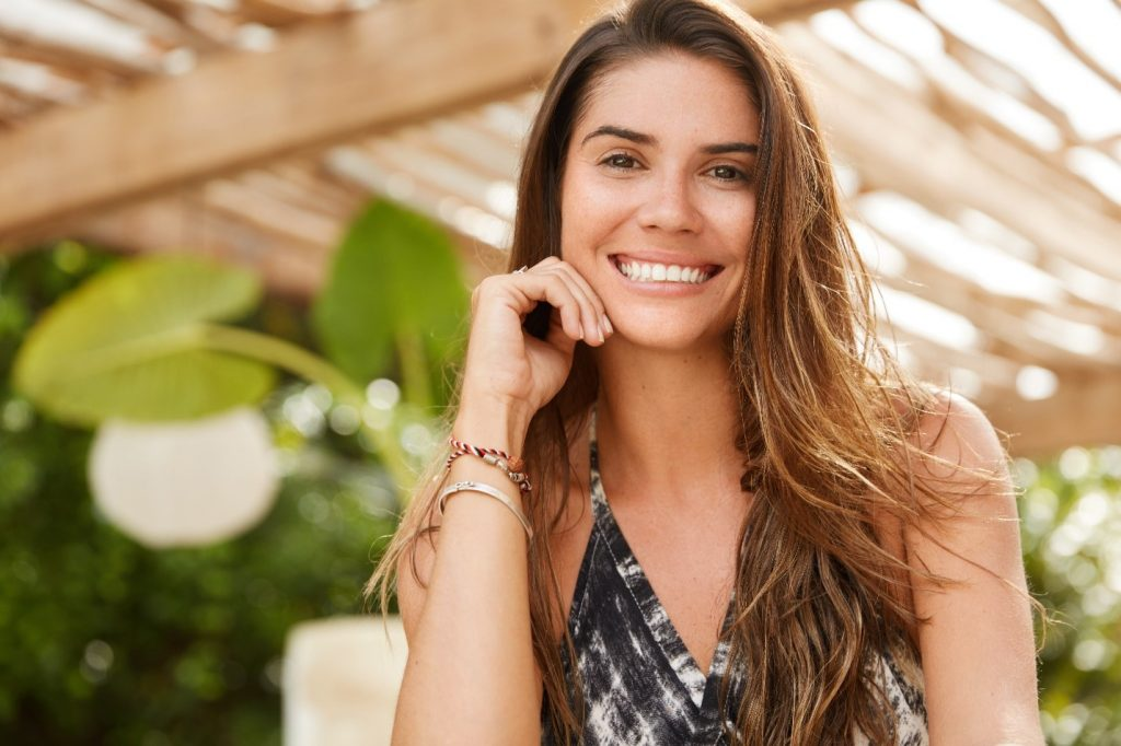 Closeup of woman with white teeth smiling outside